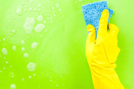 Person, a hand in a rubber glove in the picture, removes and washes, the green background copy space Stock Photo