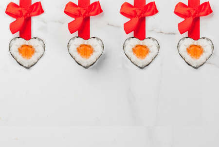 Real sushi set for valentines day in form of hearts, with red ribbon and bow. White marble background copy space top view