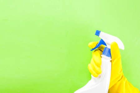 Hand im Schutzhandschuh, der Spray hält. grüner Hintergrund Kopie Raum Standard-Bild - 93158138