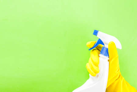 Hand in protective glove holding spray. green background copy space Stock Photo