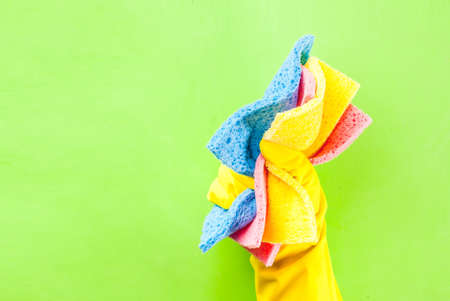 Hand in protective glove holding sponges for cleaning. green background copy space Stock Photo