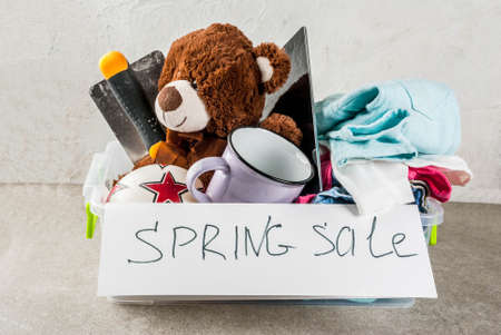Plastic spring sale box with toys, clothes gadgets and tools, white grey background copy space