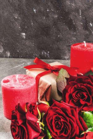 Holiday  background, Valentines day. Bouquet of red roses, tie with a red ribbon, with wrapped gift box and red candle. On a gray stone table, copy space