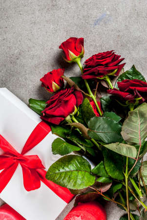 Holiday  background, Valentines day. Bouquet of red roses, tie with a red ribbon, with wrapped gift box and red candle. On a gray stone table, copy space top view Archivio Fotografico