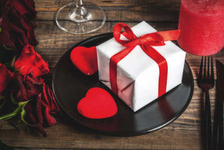 Table setting for Valentines day. Bouquet of red roses, tie with a red ribbon, gift box, red hearts, candle, plate, fork, spoon and knife. On a wooden table, copy space