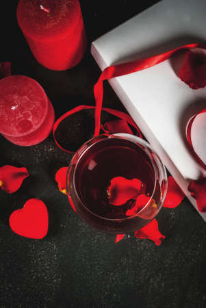 Valentines day concept, white wrapped gift box with red ribbon, rose flower petals, red wine glass, with red candle, on dark stone background, copy space top view