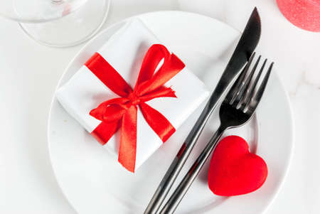 Valentines day table setting with plate, fork, knife, gift box and red heart, on white marble background copy space top view