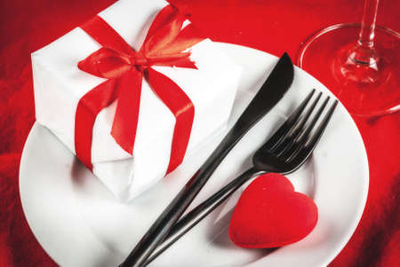 Valentines day table setting with plate, fork, knife, gift box and red heart, on red tablecloth background copy space