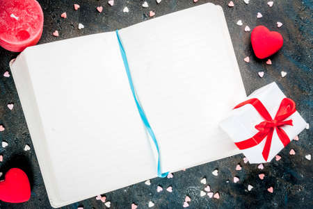 Valentines Day concept, background for congratulations with a notepad, pen and decorative sweet hearts, a red candle. Top view copy space Archivio Fotografico