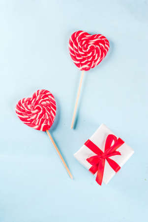 Valentines day light blue background, greeting card concept, Two red heart lollipops or sweet candy on sticks, with gift box, top view copy space Archivio Fotografico