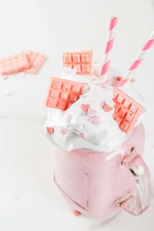 Crazy shake, romantic milkshake for Valentines day with strawberry, white chocolate and sugar candy hearts, on white background, copy space Archivio Fotografico