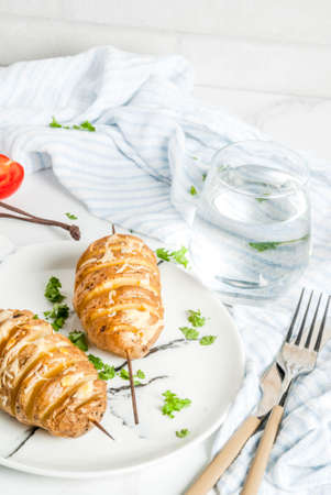 Tornado Cheesy Potatoes with Parsley and Tomatoes, on white marble background, copy space Archivio Fotografico