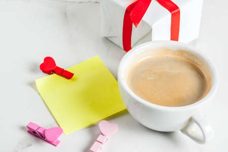 Valentines day concept, gift box with red ribbon, coffee mug, blank paper note for congratulations with heart shaped pins, white background, copy space top view