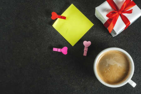 Valentines day concept, gift box with red ribbon, coffee mug, blank paper note for congratulations with heart shaped pins, black background, copy space top view
