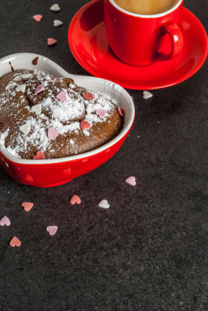 Valentines day background, red coffee mug and chocolate mug cake or brownie with powdered sugar and sweet heart shaped sprinkles, black background, copy space