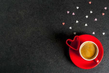 Valentines day concept, coffee mug and sweet heart shaped sprinkles, black background, copy space  top view Archivio Fotografico