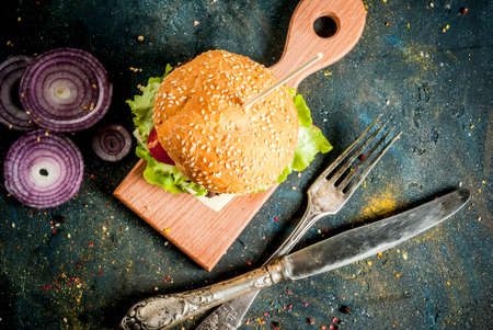 Fast food. Unhealthy food. Delicious Fresh Tasty Burgers with Beef Cutlet, fresh Vegetables and Cheese on dark blue concrete background. Copy space  top view Archivio Fotografico