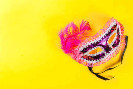 Mardi gras background with holiday mask, on bright yellow background copy space top view Foto de archivo