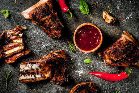 Raw fresh meat, roasted or grilled lamb or beef ribs with red tomato sauce, hot pepper, garlic and spices on dark stone background, copy space top view Archivio Fotografico