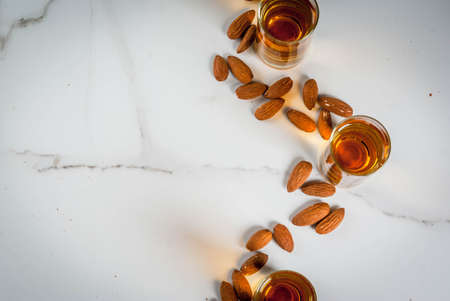 Golden almond liqueur with nuts on white marble background. top view copy space