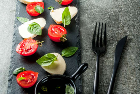 Italian dinner. Homemade salad caprese - tomatoes, fresh basil, mozzarella cheese, olive oil. On a black stone table. Served on skewers. Copy space top view Archivio Fotografico