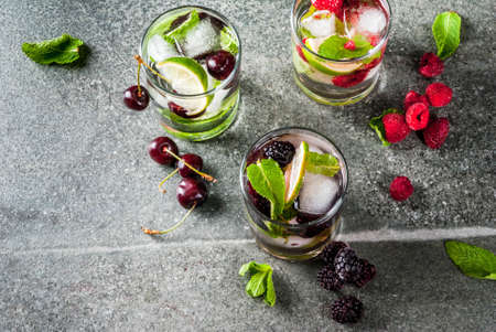 Set of traditional summer refreshing drinks berry mojito. With lime, mint leaves, blackberries, raspberries and cherries. With the ingredients on a dark stone table. Copy space Archivio Fotografico