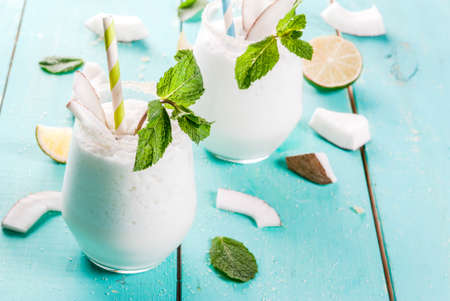 Summer refreshment drinks, cocktails. Frozen coconut mojito with lime and mint. Pina colada. On a light blue green wooden table with ingredients. Copy space