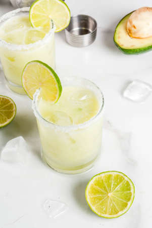 Alcoholic cocktail recipes and ideas. Avocado and lime margarita with salt, on a white marble kitchen table. Copy space Archivio Fotografico
