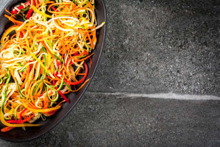 Vegan food, diet. Vegetable noodles, pasta from carrot, zucchini, bell pepper. Ready for baking cooking on a stone table. Copy space top view Archivio Fotografico
