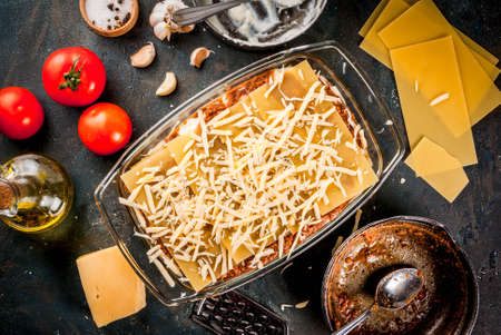 Cooking homemade classic lasagna bolognese, on dark blue table; with ingredients, top view copy space