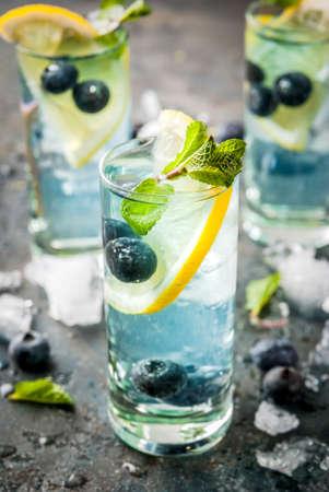 Zomerfrisdrank, bosbessenlimonade of mojito-cocktail met citroen, verse bosbessen en munt, sdarkblauwe steen achtergrond kopie ruimte Stockfoto