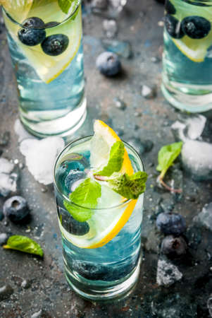 Summer refreshment drinks, Blueberry Lemonade or mojito cocktail with lemon, fresh blueberries and mint, sdark blue stone background copy space Stock Photo