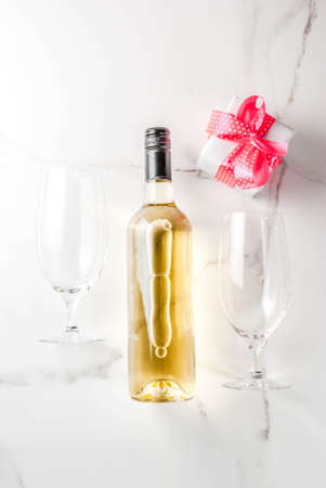 Valentines day concept with wine, two glasses and gift box on white marble background, copy space top view Stock Photo