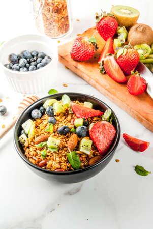 Sana colazione con muesli o muesli con noci e bacche fresche e frutta - fragola, mirtillo, kiwi, sul tavolo bianco, copia spazio