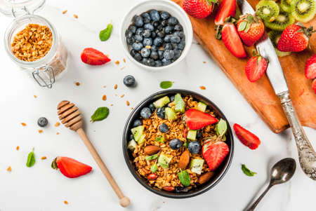 Healthy breakfast with muesli or granola with nuts and fresh berries and fruits - strawberry, blueberry, kiwi, on white table, copy space top view Archivio Fotografico