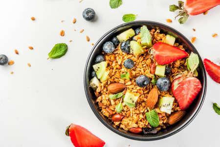 Sana colazione con muesli o muesli con noci e bacche fresche e frutta - fragola, mirtillo, kiwi, sul tavolo bianco, copia spazio vista dall'alto Archivio Fotografico