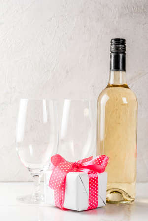 Valentines day concept with wine, two glasses and gift box on white concrete background, copy space