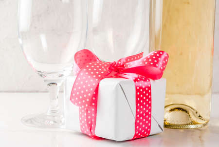 Valentines day concept with wine, two glasses and gift box on white concrete background, copy space close view