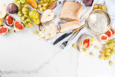 Sandwiches with ricotta or cream cheese, ciabatta, fresh figs, pears, grape, walnuts and honey on white marble table table, with wine glass copy space top view