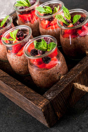 Healthy vegan breakfast. Dessert. Alternative food. Pudding with chia seeds, fresh strawberries, blackberries and mint. On a dark stone background, in an old wooden tray. Close view