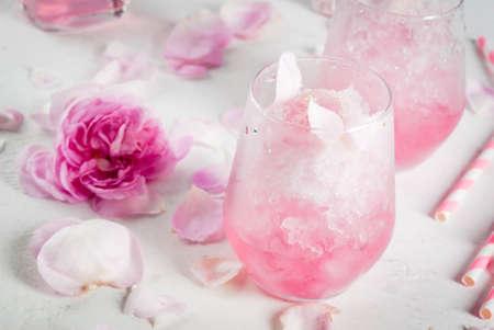 Sobremesas refrescantes de verão. Comida de dieta vegan. Sorvete congelado rosa, congelou, com pétalas de rosa e vinho rosé. Sobre uma mesa de concreto branca, com colheres, palhas listradas, pétalas e flores rosas. Espaço da cópia Foto de archivo - 93386034