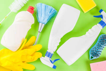 Spring cleaning concept with supplies, house cleaning products pile. Household chore concept, on green background top view