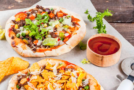Homemade Mexican Taco PIzza with Nachos  chips, beans, fresh vegetables, beef meat, copy space