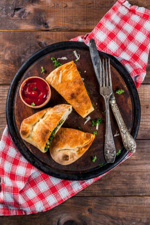 Italian food, closed pizza calzone with Spinach and Cheese, wooden background, copy space top view Archivio Fotografico