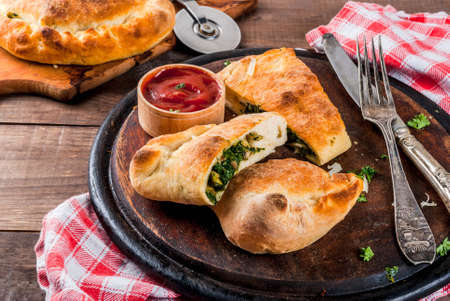 Italian food, closed pizza calzone with Spinach and Cheese, wooden background, copy space
