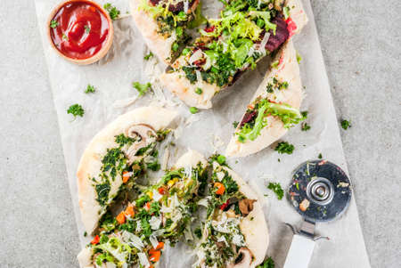 Vegan pizza with fresh vegetables and pesto, gray stone background, copy space top view