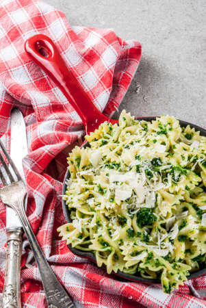 Vegan and healthy food ideas, creamy Spinach artichoke pasta with cheese, on gray stone table, copy space Standard-Bild