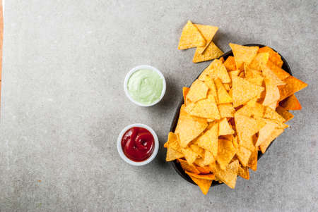 Tasty mexican snack,  tortilla chips nachos with ketchup and guacamole, grey stone table, copy space top view