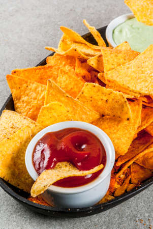 Tasty mexican snack,  tortilla chips nachos with ketchup and guacamole, grey stone table, copy space
