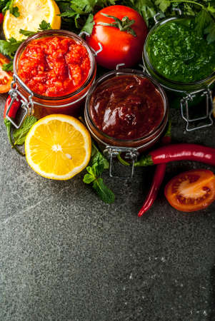 Indian traditional food, Set of three chutney for Chaat and Sev Puri - sweet date-tamarind, cilantro-mint green and red chilli garlic, On dark stone background, copy space top view Stock Photo